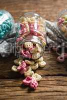 Scattered honeycomb cereals from jar on wooden table