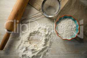 Overhead view of flour in bowl by rolling pin and strainer