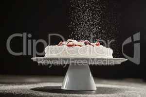 Powdered sugar falling over white cake on stand