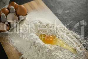 High angle view of egg yolk in flour ny carton on cutting board