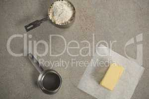 Butter on wax paper by strainer and flour in measuring cup