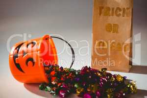 Trick or treat text on paper bag by bucket and colorful chocolates