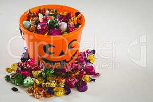 Bucket with various sweet food over white background during Halloween
