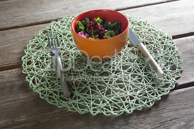 Vegetable salad in bowl on place mat at table