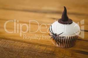 Cup cake with spider and witch hat on table