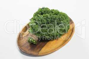 High angle view of fresh kale bundle in wooden plate