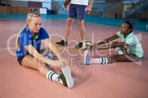 Volleyball players performing stretching exercise