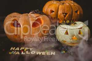 Happy Halloween text with jack o lanterns by candies and decorations