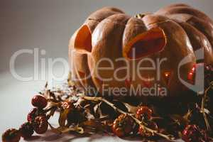 Jack o lantern with small pumpkins over white background