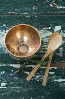 Golden steel bowl, spatula and spoon on table
