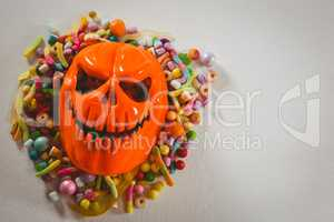 Monster mask with various candies over white background