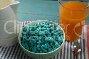 Cereal rings and orange juice on napkin cloth