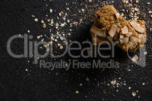 Granola bars with dried coconut and grains on black background