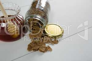 Jar of honey and wheat flakes spilling out of bottle