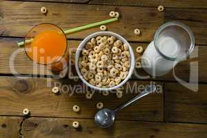 Cereal rings, orange juice and milk on wooden table
