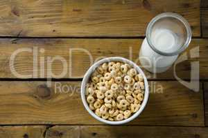 Cereal rings and milk on wooden table