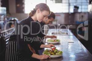 Side view of young wait staff preparing fresh salad plates while standing in commercial kitchen