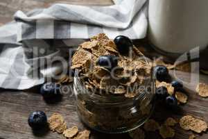 Jar filled with wheat flakes and blue berries