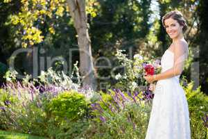 Portrait of smiling bride holding bouquet while standing on field