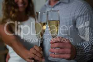 Mid section of couple holding champagne glass