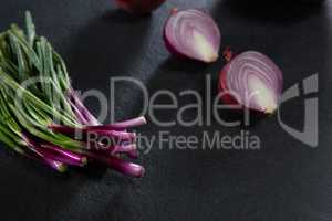 Scallions and halved of onion on black background