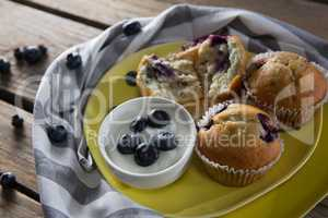 Blueberries with yogurt and muffins on plate