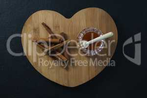 Cinnamon sticks and honey on heart shaped chopping board