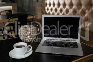 Close-up of coffee, laptop and lit candle on table
