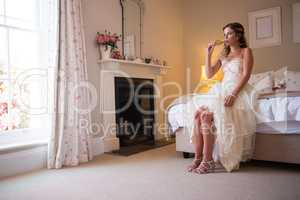 Bride drinking champagne while sitting on bed