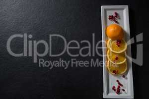 Slice of orange with pomegranate seeds in tray