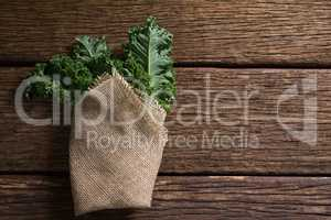 Wrapped mustard greens on wooden table