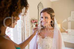 Beautician dressing up bride at home