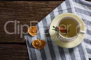 Cup of tea with cinnamon stick on napkin