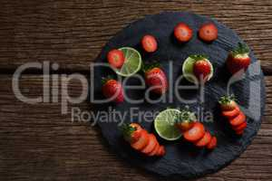 Sliced strawberries and lemon on round tray