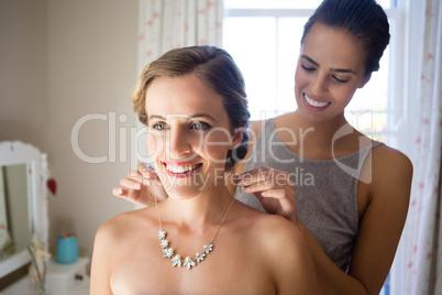Bridesmaid fastening bride necklace in room