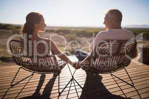 Senior couple sitting on chairs at the resort