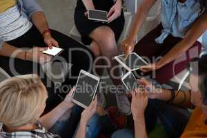 High angle view of friends using technologies
