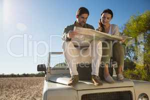Young couple holding map on tire over off road vehicle