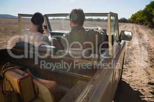 Rear view of couple in off road vehicle on landscape