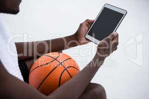 Player holding basketball while using digital tablet