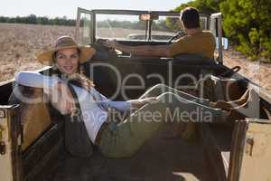 Woman relaxing with man driving off road vehicle