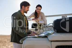 Couple reading map on off road vehicle