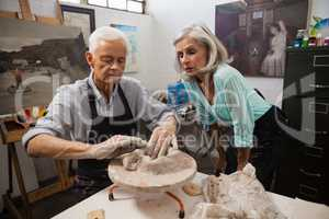 Senior woman assisting senior man in making pottery during drawing class