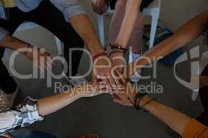 High angle view of adult students stacking hands