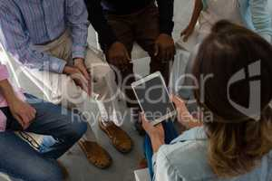 High angle view of teacher holding tablet while sitting with senior people