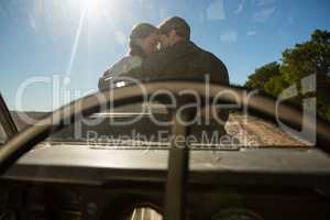 Romantic couple seen through off road vehicle windshield