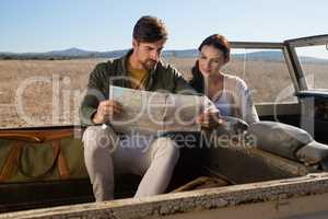 Couple reading map in off road vehicle
