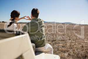 Rear view of couple making heart shape with hands on off road vehicle