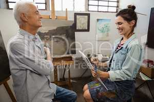 Woman interacting with senior man while sketching on canvas