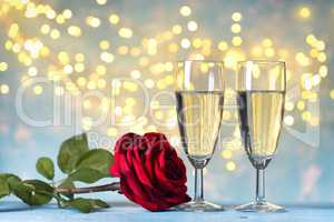 Two champagne glasses and red rose flower, against holiday lights